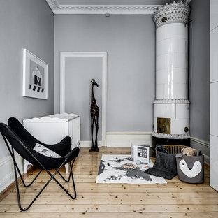 Inspiration för mellanstora nordiska könsneutrala babyrum, med grå väggar, mellanmörkt trägolv och beiget golv