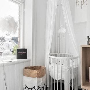 Réalisation d'une petit chambre de bébé neutre minimaliste avec un mur blanc et un sol noir.