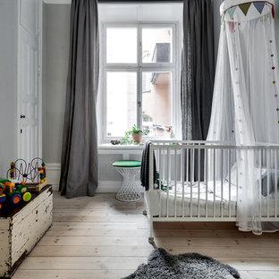 Idéer för mellanstora minimalistiska könsneutrala babyrum, med grå väggar, ljust trägolv och beiget golv