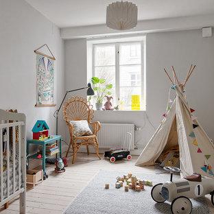 Idéer för ett mellanstort nordiskt könsneutralt babyrum, med grå väggar, ljust trägolv och beiget golv