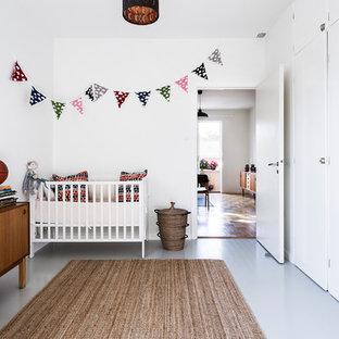 Foto på ett mellanstort skandinaviskt könsneutralt babyrum, med vita väggar, målat trägolv och grått golv