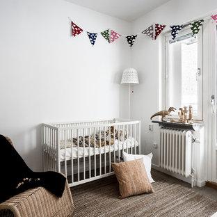 Idéer för att renovera ett mellanstort nordiskt könsneutralt babyrum, med vita väggar och brunt golv