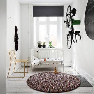 Nordisk inredning av ett mellanstort könsneutralt babyrum, med vita väggar, målat trägolv och vitt golv