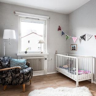 Idéer för mellanstora nordiska könsneutrala babyrum, med grå väggar och mellanmörkt trägolv