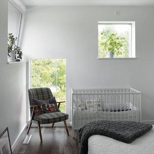 Cette photo montre une chambre de bébé neutre tendance de taille moyenne avec un mur blanc, un sol en bois foncé et un sol marron.