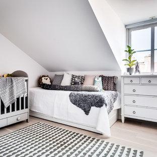 Inredning av ett skandinaviskt könsneutralt babyrum, med vita väggar, ljust trägolv och beiget golv