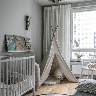 Inspiration för minimalistiska könsneutrala babyrum, med vita väggar, ljust trägolv och beiget golv
