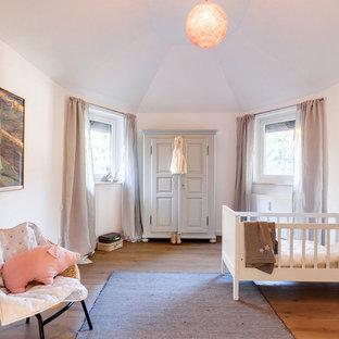Mittelgroßes, Neutrales Nordisches Babyzimmer mit weißer Wandfarbe, braunem Holzboden und braunem Boden in München
