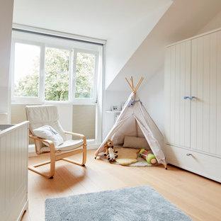 Mittelgroßes Skandinavisches Babyzimmer mit weißer Wandfarbe, hellem Holzboden und beigem Boden in Bremen
