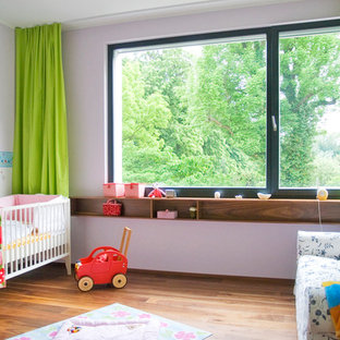 Inspiration for a medium sized contemporary gender neutral nursery in Leipzig with white walls and dark hardwood flooring.