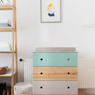 Modelo de habitación de bebé neutra nórdica con paredes blancas y suelo de madera pintada