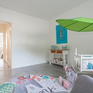 Aménagement d'une petit chambre de bébé scandinave avec un mur blanc, sol en stratifié, un sol gris et un plafond décaissé.