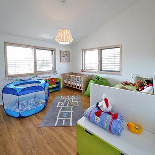 Mittelgroßes Modernes Babyzimmer mit weißer Wandfarbe, braunem Holzboden und braunem Boden in München