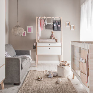 Idée de décoration pour une petit chambre de bébé fille nordique avec un mur marron, un sol en bois clair et un sol beige.