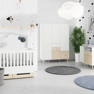 Diseño de habitación de bebé neutra nórdica, grande, con paredes blancas, suelo de cemento y suelo gris