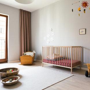 Mittelgroßes, Neutrales Skandinavisches Babyzimmer mit grauer Wandfarbe, hellem Holzboden und beigem Boden in Berlin