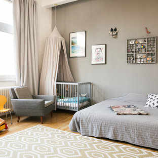 Design ideas for a mid-sized contemporary gender-neutral nursery in Berlin with grey walls, medium hardwood floors and brown floor.