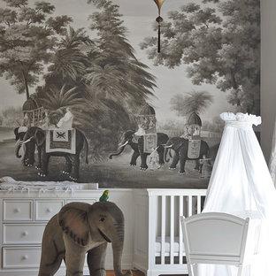 Ejemplo de habitación de bebé neutra exótica, de tamaño medio, con suelo de madera en tonos medios y paredes grises