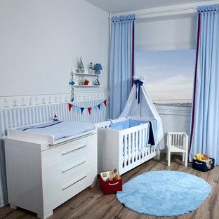 Ispirazione per una cameretta per neonato costiera con pareti blu, parquet scuro e pavimento marrone