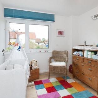Modernes Babyzimmer mit weißer Wandfarbe, hellem Holzboden und beigem Boden in Stuttgart