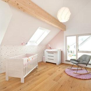 Großes Modernes Babyzimmer mit weißer Wandfarbe, hellem Holzboden und braunem Boden in Stuttgart