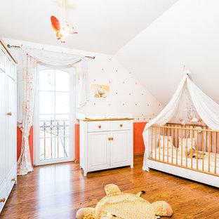 Идея дизайна: комната для малыша среднего размера в классическом стиле с красными стенами, деревянным полом и коричневым полом для девочки