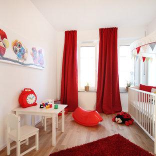 Ispirazione per una cameretta per neonati neutra minimal di medie dimensioni con pavimento in legno massello medio, pareti beige e pavimento beige