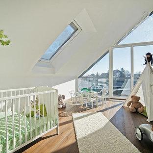 Neutrales, Mittelgroßes Modernes Babyzimmer mit weißer Wandfarbe, braunem Holzboden und braunem Boden in München
