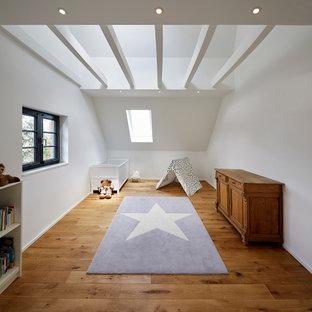 Modelo de habitación de bebé neutra de estilo de casa de campo, de tamaño medio, con paredes blancas, suelo de madera en tonos medios y suelo marrón