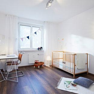 Mittelgroßes Modernes Babyzimmer mit weißer Wandfarbe, dunklem Holzboden und braunem Boden in Nürnberg