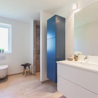Großes Nordisches Duschbad mit integriertem Waschbecken, flächenbündigen Schrankfronten, bodengleicher Dusche, Wandtoilette, weißen Schränken, weißer Wandfarbe, Betonboden und Laminat-Waschtisch in Kopenhagen
