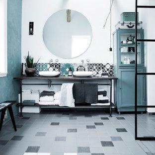 Immagine di una stanza da bagno contemporanea di medie dimensioni con consolle stile comò, ante blu, piastrelle di cemento e top in acciaio inossidabile