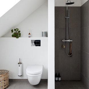 Immagine di una stanza da bagno con doccia nordica di medie dimensioni con doccia alcova, WC sospeso, piastrelle grigie, pavimento in cemento, pavimento grigio, doccia aperta e pareti bianche