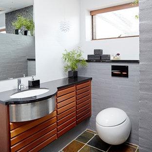 Ejemplo de cuarto de baño principal, actual, con puertas de armario de madera oscura, sanitario de pared, baldosas y/o azulejos grises, suelo de baldosas tipo guijarro, paredes blancas, lavabo bajoencimera, suelo multicolor y encimeras negras