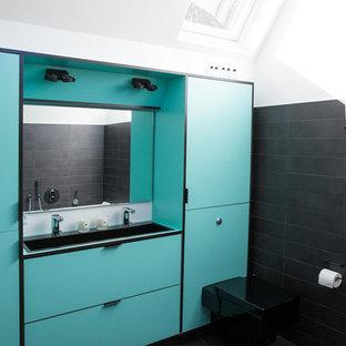 Esempio di una stanza da bagno contemporanea di medie dimensioni con ante lisce, ante turchesi, WC sospeso, pareti nere, lavabo rettangolare e pavimento nero
