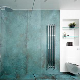 Modelo de cuarto de baño actual, de tamaño medio, con baldosas y/o azulejos azules, ducha abierta, armarios abiertos, sanitario de pared, paredes azules y suelo turquesa