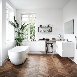 Imagen de cuarto de baño principal, nórdico, grande, con armarios con paneles lisos, puertas de armario blancas, bañera exenta, paredes blancas, suelo de madera oscura y suelo marrón