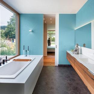 Imagen de cuarto de baño principal, actual, grande, con lavabo integrado, armarios con paneles lisos, puertas de armario de madera oscura, bañera encastrada, paredes azules, baldosas y/o azulejos negros, baldosas y/o azulejos de cemento y encimera de acrílico