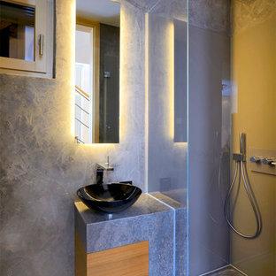 Modelo de cuarto de baño con ducha, actual, pequeño, con lavabo sobreencimera, armarios con paneles lisos, puertas de armario de madera oscura, encimera de granito, ducha a ras de suelo, baldosas y/o azulejos grises, paredes grises y suelo de pizarra