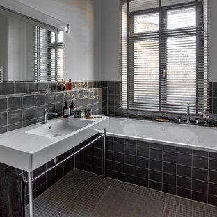 Mittelgroßes Modernes Badezimmer mit Einbaubadewanne, schwarzen Fliesen, Keramikfliesen, weißer Wandfarbe, Keramikboden, grauem Boden und Waschtischkonsole in Berlin