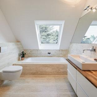 Стильный дизайн: маленькая ванная комната в современном стиле с плоскими фасадами, белыми фасадами, накладной ванной, инсталляцией, белыми стенами, полом из травертина, настольной раковиной, столешницей из дерева, плиткой из травертина и коричневой столешницей - последний тренд