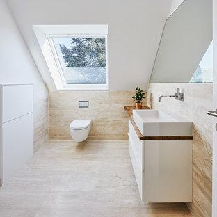 Mittelgroßes Modernes Badezimmer mit flächenbündigen Schrankfronten, weißen Schränken, Wandtoilette, weißer Wandfarbe, Travertin, Aufsatzwaschbecken, Waschtisch aus Holz und brauner Waschtischplatte in Düsseldorf