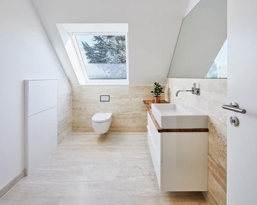 Mittelgroßes Modernes Badezimmer Mit Flächenbündigen Schrankfronten, Weißen  Schränken, Wandtoilette, Weißer Wandfarbe, Travertin