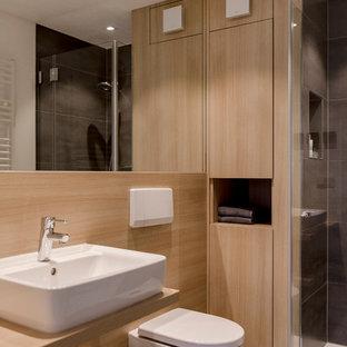 Modernes Duschbad mit flächenbündigen Schrankfronten, hellen Holzschränken, bodengleicher Dusche, Wandtoilette, grauen Fliesen, brauner Wandfarbe, Aufsatzwaschbecken, Waschtisch aus Holz, grauem Boden, offener Dusche und brauner Waschtischplatte
