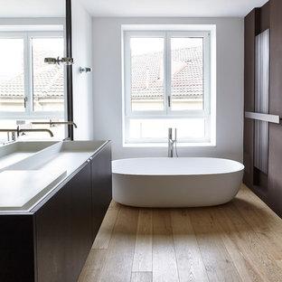 Mittelgroßes Modernes Badezimmer En Suite mit flächenbündigen Schrankfronten, dunklen Holzschränken, freistehender Badewanne, hellem Holzboden, weißer Wandfarbe, Mineralwerkstoff-Waschtisch und Trogwaschbecken in München