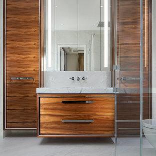 Mittelgroßes Modernes Duschbad mit flächenbündigen Schrankfronten, hellbraunen Holzschränken, Eckdusche, grauem Boden, Falttür-Duschabtrennung, grauer Waschtischplatte, Einzelwaschbecken und schwebendem Waschtisch in Berlin