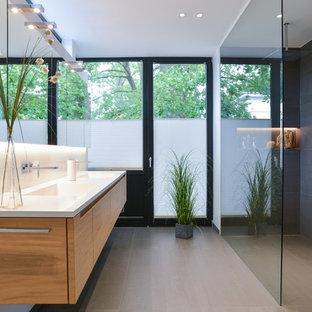 Großes Modernes Duschbad mit flächenbündigen Schrankfronten, braunen Schränken, bodengleicher Dusche, Wandtoilette mit Spülkasten, grauen Fliesen, Steinfliesen, grauer Wandfarbe, Mineralwerkstoff-Waschtisch, grauem Boden, offener Dusche und integriertem Waschbecken in Köln