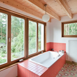 Example of a mid-sized danish red tile and ceramic tile ceramic floor, green floor and wood ceiling drop-in bathtub design in Berlin with white walls