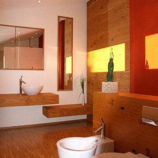 ミュンヘンの中サイズのアジアンスタイルのおしゃれなバスルーム (浴槽なし) (インセット扉のキャビネット、ベージュのキャビネット、壁掛け式トイレ、赤い壁、淡色無垢フローリング、ベッセル式洗面器、木製洗面台、ベージュの床) の写真
