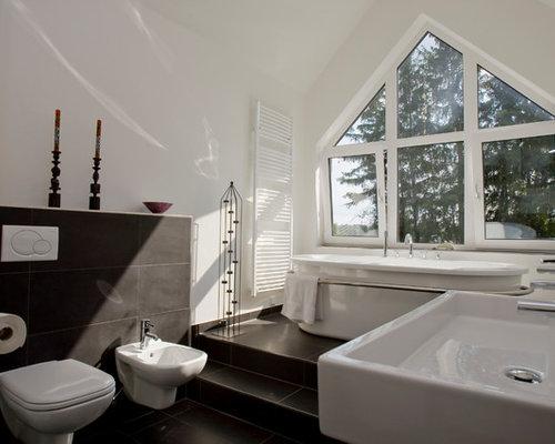 Mittelgroßes Modernes Badezimmer Mit Freistehender Badewanne, Wandtoilette,  Grauen Fliesen, Weißer Wandfarbe Und Wandwaschbecken